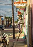 Facade renovations in trinidad. Old man on a ladder painting the colorful facade or a house Royalty Free Stock Photography