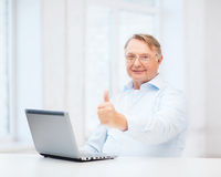 Old man with laptop computer showing thumbs up Stock Photos