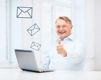Old man with laptop computer showing thumbs up Stock Image