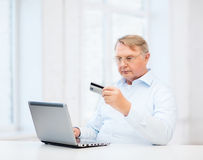 Old man with laptop and credit card at home Royalty Free Stock Photo