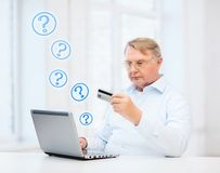 Old man with laptop and credit card at home Stock Photos