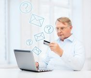 Old man with laptop and credit card at home Stock Photo