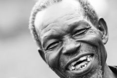 An old man laughing with no teeth. An old man, brother, father, grandfather, with a big grin showing teeth in Gulu Uganda stock image