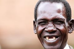 An old man laughing with no teeth. An old man, brother, father, grandfather, with a big grin showing teeth in Gulu Uganda royalty free stock image