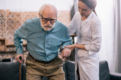Old man leaning on cane and female stock images
