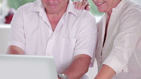 Old man learning to use laptop with partner stock footage