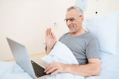 The old man lies on a cot in the medical ward and communicates with someone via video link via a laptop. Stock Photo
