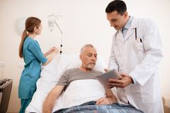 The old man lies on a cot in medical ward, and next to him stands a doctor. He is showing something to old man on tablet. The old men lies on a cot in the Stock Photos
