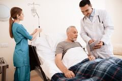 The old man lies on a cot in medical ward, and next to him stands a doctor. He is showing something to old man on tablet. The old men lies on a cot in the Royalty Free Stock Photo