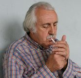 Old Man Lightening A Cigarette royalty free stock photos