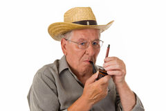 Old man lighting up a pipe Stock Images