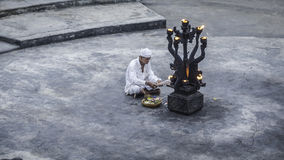 Old man lights a fire at Uluwatu temple, Bali Stock Image