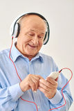 Old man listening music on headphones Stock Photos
