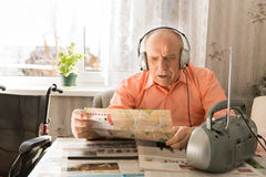 Old Man Listening Music From Radio While Reading Royalty Free Stock Photo