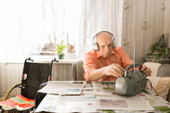 Old Man Listening News on Radio with Headset Stock Image
