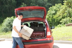 Old man loads his car`s suitcases Royalty Free Stock Photography