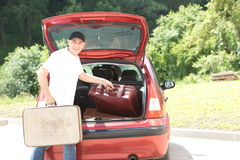 Old man loads his car`s suitcases Royalty Free Stock Photo