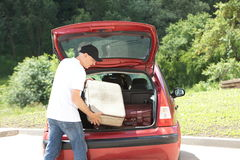Old man loads his red car suitcases. A man loads his car`s suitcases Stock Images