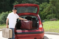 Old man loads his red car suitcases Royalty Free Stock Photo