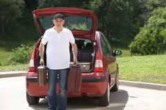 Old man loads his red car suitcases Royalty Free Stock Photography