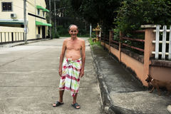 Old man with loincloth standing on public street. Rural scene Royalty Free Stock Photo