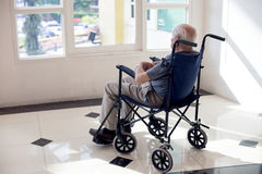 Old man lonely. Old man sit on wheelchair looking out to from the room fill lonely waiting for take care white room dementia and alzheimer Stock Image