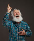 Old man with a long beard with big smile. On a dark background royalty free stock images