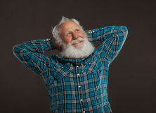 Old man with a long beard with big smile. On a dark background royalty free stock image