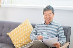 Old man look by magnifier. Old asian man look somrthing by magnifier at home stock photography