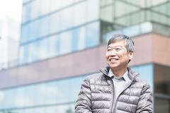 Old man look somewhere. Old man smile happily and look somewhere with business building stock images