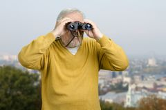 Old man looking through binocular on the city view. Senior tourist observing city locations using binoculars Stock Photography
