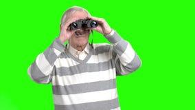 Old man looking through binocular. Grandpa with binocular, green hroma background stock video footage