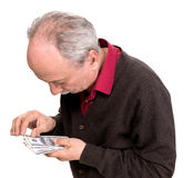 Old man looking at dollar bills. On a white background Stock Images
