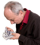 Old man looking at dollar bills. On a white background Stock Photos