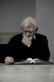 Old man looking at photo album Stock Photo
