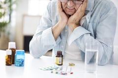 Old man looking at pills desperately Stock Photo