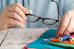 Old man looking on sew needle throw glasses royalty free stock images