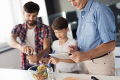 The old man is looking at something on the tablet, while behind him the boy and man are finishing the salad preparation. A boy and a men prepare a salad for Stock Photos