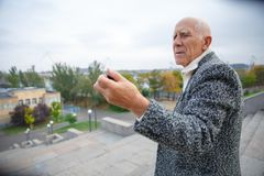 The old man looks at the action camera he holds in his hand. Outdoors on the street. stock photography