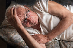 Old man lying in bed Stock Photos