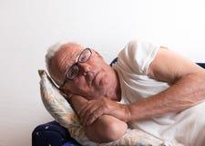 Old man resting on sofa stock image
