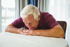 An old man is lying on the table. In a retirement home Stock Image