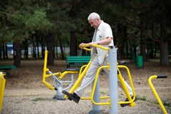 Old man making exercises on outdoor gym. Stock Image