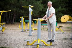 Old man making exercises on outdoor gym. Royalty Free Stock Photography
