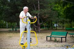 Old man making exercises on outdoor gym. Stock Photos