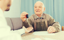 Old man and man signed contract car lease. Elderly men and young men sign contract car rent and hand over keys stock image