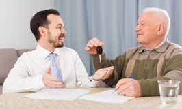 Old man and manager signed contract car lease. Elderly men and manager signed contract car hire at home and hand over keys Stock Image