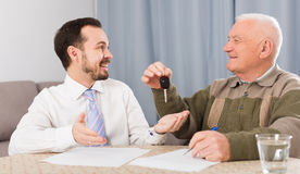 Old man and manager signed contract car lease. Old men and manager signed contract car lease at home and hand over keys royalty free stock photography
