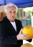Old man at the marketplace. Picking a melon Stock Photo