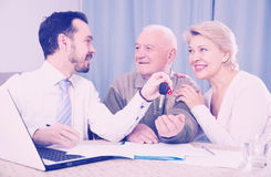 Old man and mature woman signing contract car lease. Elderly men and manager signed contract car hire and get keys from agent royalty free stock photo